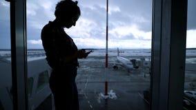 Het silhouet van jongelui paste meisje status dichtbij luchthavenvenster en het gebruiken van haar smartphone Goed gevormd jong b stock videobeelden
