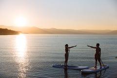 Het silhouet van mannetje en het wijfje op sup branding verenigen handen bij de oceaan Conceptenlevensstijl, sport, liefde Stock Foto's