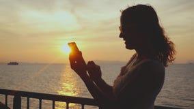 Het silhouet van meisje gebruikt mobiele telefoon terwijl het reizen op cruiseschip bij verbazende zonsondergang Langzame Motie 1 stock videobeelden
