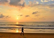 Het silhouet van mensen stoot op de achtergrond van de strandzonsondergang aan Royalty-vrije Stock Afbeeldingen