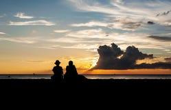 Het silhouet van minnaars ontspant op het strand stock fotografie