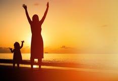 Het silhouet van moeder en weinig dochter overhandigt omhoog royalty-vrije stock fotografie