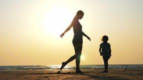 Het silhouet van moeder onderwijst haar weinig dochter om te dansen bewegingen stock video