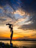 Het silhouet van ontspant vrouwen status en rivier Stock Fotografie