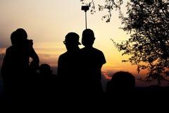 Het silhouet van Reizigers geniet van Hun Ogenblik het Letten op Zonsondergang stock foto's