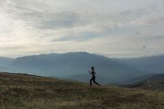 Het silhouet van slank meisje stoot in mistige bergen aan stock foto