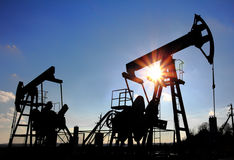 Het silhouet van twee oliepompen Stock Foto