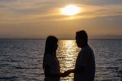 Het silhouet van twee volwassenen voor jonge paren omhelst de samen gelukkige taille stock afbeelding