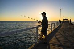 Het silhouet van visser met hoed en vissenstaaf die zich op overzees dok bevinden die bij zonsondergang met mooie oranje hemel in Royalty-vrije Stock Foto