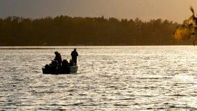 Het silhouet van vissers die een snoek van paarsnoekbaarzen vangen vist terwijl in een vissersboot op een meer bij zonsondergang stock footage