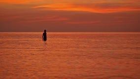 Het silhouet van vrouw bewondert zonsondergang in het overzees, langzame motie 1920x1080 stock video