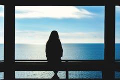 Het silhouet van vrouwen die en kijkt het overzees zitten royalty-vrije stock foto's