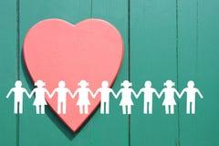 Het silhouet van Witboekkinderen op groene houten achtergrond met rood hart stock afbeeldingen