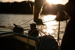 Het silhouet van zeelieden overhandigt op een krukkabel op een zeilboot op een zonsondergang Schot met een selectieve nadruk royalty-vrije stock foto