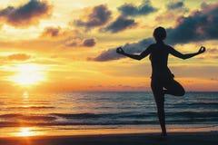 Het silhouet verbazende zonsondergang van de yogavrouw op het overzeese strand ontspan royalty-vrije stock afbeeldingen