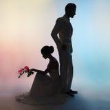 Het silhouetbruidegom en bruid van het huwelijkspaar op kleurenachtergrond Royalty-vrije Stock Afbeeldingen