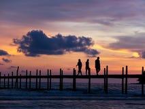 Het silhouetcijfer van mensen die ontspant op een grote teakwood brid lopen Royalty-vrije Stock Afbeelding