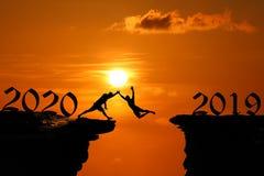 Het Silhouetconcept nieuw jaar 2020 die, Mens en in het hol of de hoge klippen bij een rode hemelzonsondergang springen beklimmen stock afbeeldingen