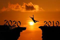 Het Silhouetconcept nieuw jaar 2020 die, Mens en in het hol of de hoge klippen bij een rode hemelzonsondergang springen beklimmen royalty-vrije stock fotografie