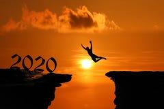 Het Silhouetconcept nieuw jaar 2020 die, Mens en in het hol of de hoge klippen bij een rode hemelzonsondergang springen beklimmen royalty-vrije stock afbeeldingen