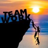 Het silhouetgroepswerk van mensen beklimt in klip om het WERK van het woordteam met zonsopgang te bereiken stock afbeeldingen