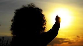 Het silhouetmeisje bij zonsondergang vangt de zon, stock video