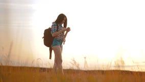 Het het silhouetmeisje van de Hipsterwandelaar schiet video van mooie aardzonsondergang op smartphone langzame motie van de celte stock videobeelden