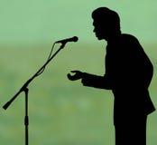 Het silhouettoespraak van de mens aan microfoon Stock Fotografie