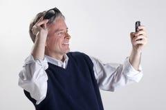 Het similing van de mens aan cellphone royalty-vrije stock afbeeldingen