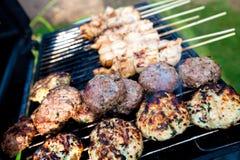 Het sissen van burgers en kip kebabs Stock Foto's