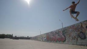 Het skateboard ontbreekt Skateboarder die en onderaan het doen van trucs in een straat met een skateboard rijden vallen Langzame  stock footage
