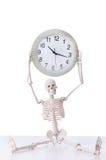 Het skelet met klok op wit wordt geïsoleerd dat Stock Foto