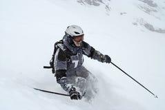 Het skiån (Mens in grijs skikostuum) Stock Afbeelding