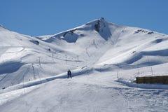 Mens die op sneeuwberg ski?t stock foto