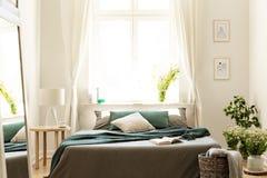 Het slaapkamerbinnenland in aardkleuren met groot bed, grijze en groene linnen en hoofdkussens, verse weide bloeit en een zonnig  royalty-vrije stock foto's