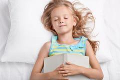 Het slaapmeisje ligt in bed, houdt boek op borst, viel in slaap na het lezen van sprookje, ligt op wit beddegoed, heeft goede rus stock afbeelding