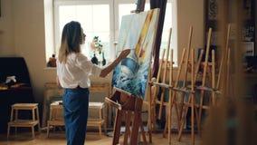 Het slanke blonde meisje schildert beeld met olieverven die borstel houden en zeegezicht afschilderen binnen werkend in werkruimt stock video