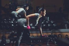 Het slanke, bodybuildermeisje, heft zware domoor op die zich voor de spiegel bevinden terwijl opleiding in de gymnastiek Royalty-vrije Stock Foto's