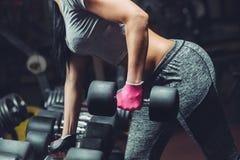 Het slanke, bodybuildermeisje, heft zware domoor op die zich voor de spiegel bevinden terwijl opleiding in de gymnastiek Stock Afbeelding