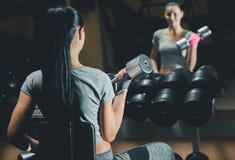 Het slanke bodybuildermeisje heft zware domoor op die zich voor de spiegel bevinden terwijl opleiding in de gymnastiek Stock Foto's