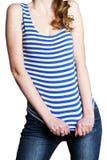 Het slanke cijfer van het meisje in het gestreepte overhemd en de jeans stock foto