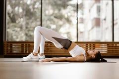 Het slanke donker-haired meisje gekleed in witte sportenkleren heeft op de mat voor fitness in de gymnastiek uitwerken stock foto's