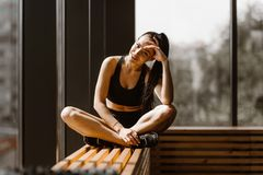 Het slanke donker-haired meisje gekleed in zwarte sportenbovenkant en borrels zit in lotusbloem stelt op een houten venstervenste stock afbeelding
