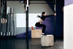 Het slanke donker-haired meisje gekleed in zwarte sportenkleren doet hurkzit op de doos in de gymnastiek stock afbeelding