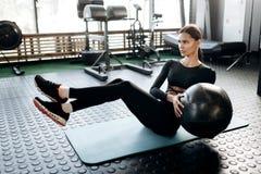 Het slanke donker-haired meisje kleedde zich in zwarte sportenkleren die oefeningen voor de pers op de mat voor fitness met fitne stock foto