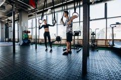 Het slanke donker-haired meisje kleedde zwarte sportenkleren en de atletische mens spreekt in de ruime gymnastiek naast de oefeni stock foto