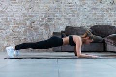 Het slanke jonge brunette die zwarte gymnastiekkleding dragen die buikbrug of voorplank doen oefent in zolderflat uit royalty-vrije stock afbeeldingen