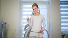 Het slanke magere meisje meet taille met blauw en geel lint Kaukasische aantrekkelijke vrouwentribunes op de schalen stock footage