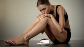 Het slanke meisje die cake bekijken, aarzelend te eten, het disciplineren let op en lichaam stock afbeeldingen