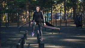 Het slanke meisje doet aërobe sporten in openlucht stappend meer dan metaalbars op sport-grond in park alleen opleidend actief stock video